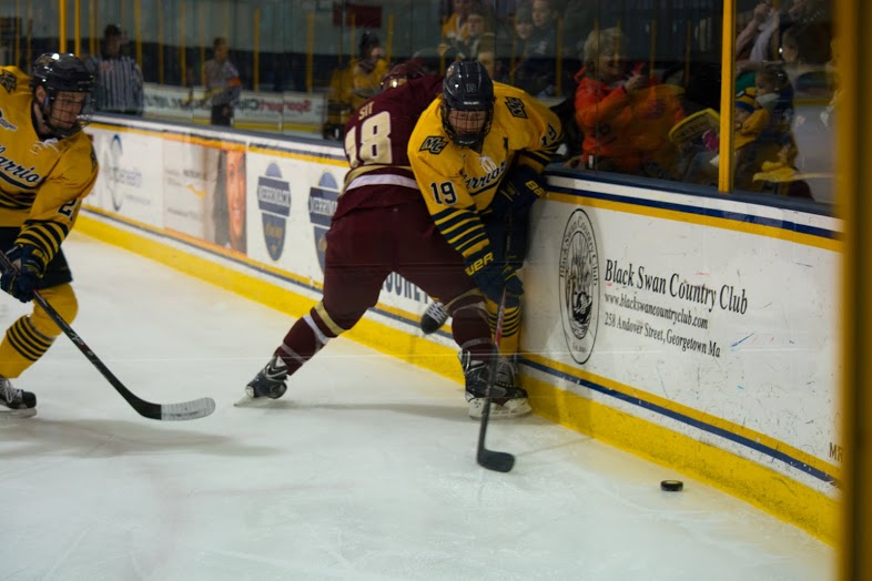 Rhett Bly (19) and John Gustafsson (28) battle in the corners against BC. Photo by Kelli Readey